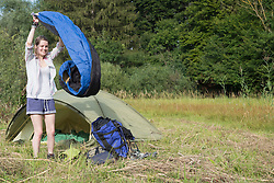 Young woman shaking the sleeping bag and smiling in forest, Bavaria, Germany