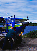 Lee Fink hand propping Lake Clark Air Service's L9B Stinson, Naknek, Alaska.