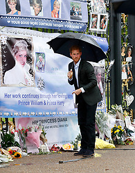 Prince Harry looks at tributes to Diana, Princess of Wales attached to the Golden Gates of Kensington Palace, London, ahead of the 20th anniversary of his mother's death.