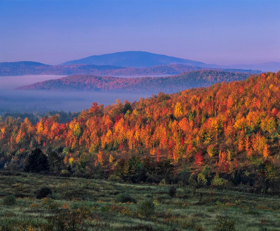 First light on hillsides of fall foliage, mountain ridgelines, and fog in valleys, Clarkesville, NH
