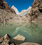 """Lago Pollone reflects Cerro Fitz Roy & Aguja Pollone, near El Chalten, in Santa Cruz Province, Argentina, Patagonia, South America. We hiked the scenic Rio Electrico Valley to Refugio Piedra del Fraile (""""Stone of the Friar"""", 14.5 km round trip). From the refuge, a rewarding day hike visits Lago Pollone (8.5 km round trip with 320 m gain). Monte Fitz Roy is also known as Cerro Chaltén, Cerro Fitz Roy, or Mount Fitz Roy. The first Europeans recorded as seeing Mount Fitz Roy were the Spanish explorer Antonio de Viedma and his companions, who in 1783 reached the shores of Viedma Lake. In 1877, Argentine explorer Francisco Moreno saw the mountain and named it Fitz Roy in honour of Robert FitzRoy who, as captain of HMS Beagle, had travelled up the Santa Cruz River in 1834 and charted large parts of the Patagonian coast. Mt Fitz Roy was first climbed in 1952. Cerro is a Spanish word meaning hill, while Chaltén comes from a Tehuelche word meaning """"smoking mountain"""", due to clouds that usually form around the peak. This image was stitched from multiple overlapping photos."""