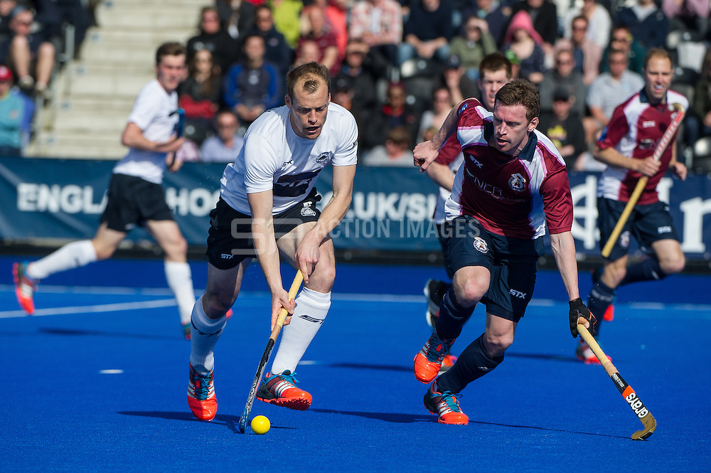 East Grinstead's Mark Pearn is watched by Michael Hoare of Wimbledon. East Grinstead v Wimbledon -  Now: Pensions Men's Hockey League Championship Final, Lee Valley Hockey & Tennis Centre, London, UK on 12 April 2015. Photo: Simon Parker