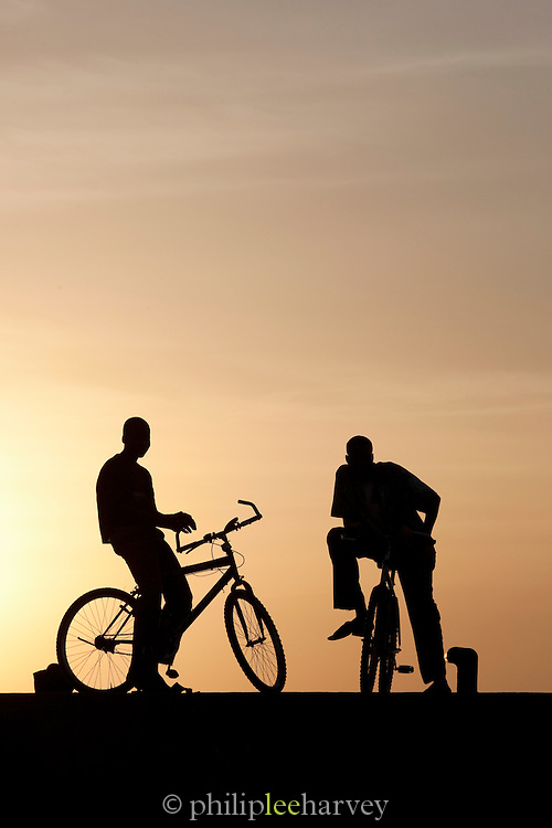 Silhouettes of men on bicycles at the busy dock on the Niger River early in the morning, at Segou, Mali