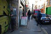 Street Scene of a man having a cigarette break beside graffiti on Wardour Street in Soho, London, England, United Kingdom.