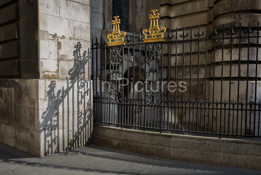 Sunlit railings of St. Mary Woolnoth church on Lombard Street, on 10th May 2017, in the City of London, England. St. Mary Woolnoth is an Anglican church in the City of London, located on the corner of Lombard Street and King William Street near Bank junction. The present building is one of the Queen Anne Churches, designed by Nicholas Hawksmoor. The churchs site has been used for worship for at least 2,000 years; traces of Roman and pagan religious buildings have been discovered. The present building is at least the third church on the site. The Norman church survived until 1445, when it was rebuilt, with a spire added in 1485. It was badly damaged in 1666 in the Great Fire of London but was repaired by Sir Christopher Wren.
