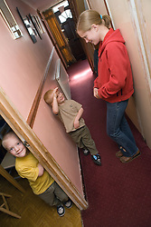 Older sister talking to her younger brothers in the hallway at home,