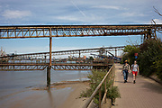An old wooden jetty and metal gantries show of an industrial past and present on the River Thames in London, United Kingdom. Here, aggregate is taken to and from ships.