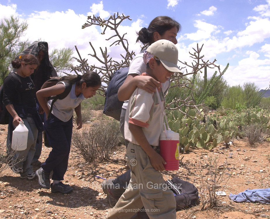 Irma Hernandez Juarez, 28, clutches her son, Enrique, 6, as they and other family walk through the West Desert on the Tohono O'odham Reservation after a Border Patrol helicopter pilot spotted them east of Sells and south of Route 86.  The group of illegal immigrants from Mexico walked for about 24 miles.  (PHOTO: NORMA JEAN GARGASZ)