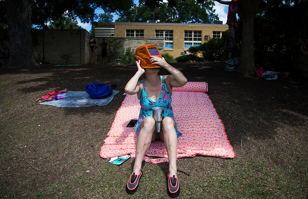 Christy Campbell views the solar eclipse through her husband's welding helmet at Barton Springs Pool on Monday, Aug. 21, 2017,  in Austin, Texas. Campbell, who is from Houston, said she and her family were planning on traveling to Oklahoma to view the eclipse, but settled on Austin to enjoy the astronomical event next to a natural springs pool. NICK WAGNER / AMERICAN-STATESMAN