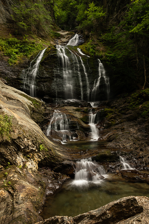 The towering cascades of Moss Glen Falls flowing on a summer afternoon in the forests of Stowe.
