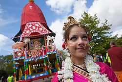 © licensed to London News Pictures. London, UK 17/06/2012. A girl posing next to a 40-foot high colourful chariot as people celebrating Hare Krishna, an old Hindu tradition in central London, today (17/06/12). Photo credit: Tolga Akmen/LNP