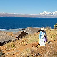 South America, Bolivia, Moon Island. Woman and dog on Moon Island of Lake Titicaca.