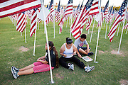 """10 SEPTEMBER 2011 - TEMPE, AZ:     KYLYNN TOM, 12, from SanTan Valley, AZ, her aunt, ALANA SMITH, from Gilbert, AZ, and brother, DAMON TOM, 14, sit in the Healing Field in Tempe, AZ, Saturday.  The """"Healing Field,"""" a display of 2,996 flags, one for each person killed in the September 11 terrorists attacks on the World Trade Center in New York City and Washington DC, have become an annual tradition in Tempe, AZ. The event is sponsored by the National Exchange Club.     PHOTO BY JACK KURTZ"""