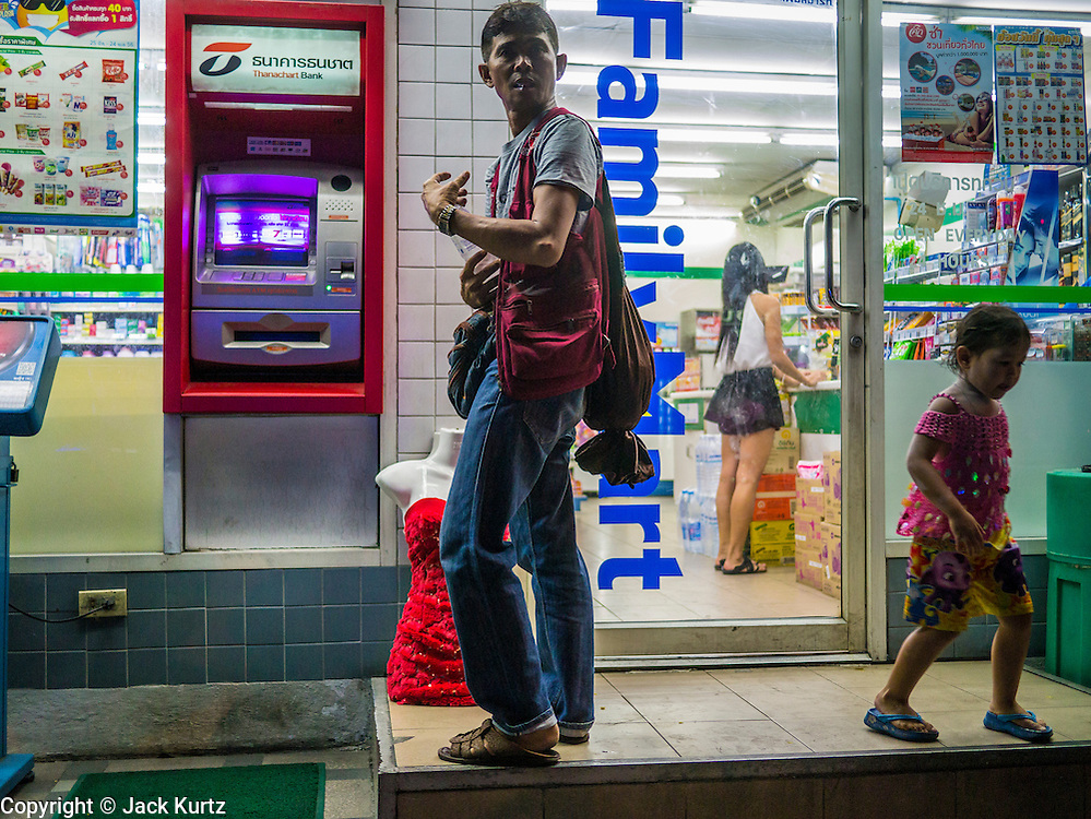 20 APRIL 2013 - BANGKOK, THAILAND:  A man who sells dresses and clothes to entertainers and sex workers in Bangkok's nightlife areas leaves a convenience store after buying an energy drink at a convenience store on Sukhumvit Soi 22.  PHOTO BY JACK KURTZ