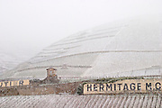 A tool shed, sign with Hermitage, the Chante Alouette vineyard. The Hermitage vineyards on the hill behind the city Tain-l'Hermitage, on the steep sloping hill, stone terraced. Sometimes spelled Ermitage. Vineyards under snow in seasonably exceptional weather in April 2005. Tain l'Hermitage, Drome, Drôme, France, Europe
