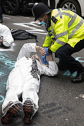 London, UK. 3rd September, 2020. A Metropolitan Police officer issues a warning to a climate activist from Extinction Rebellion wearing a hazmat suit who had occupied the street outside the Department of Transport in protest against roadbuilding. Extinction Rebellion activists are attending a series of September Rebellion protests around the UK to call on politicians to back the Climate and Ecological Emergency Bill (CEE Bill) which requires, among other measures, a serious plan to deal with the UK's share of emissions and to halt critical rises in global temperatures and for ordinary people to be involved in future environmental planning by means of a Citizens' Assembly.