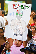 July 13, 2008 -- PHOENIX, AZ: A young Lucha Libre fan holds up a poster for Fly Boy, a Luchador tecnico (good guy wrestler) during a Lucha Libre show at El Gran Mercado in Phoenix. Lucha Libre is Mexican style wrestling. There are heros (Tecnicos) and villians (Rudos). The masks are popular as children's gifts and tourist mementos. As the size of the Mexican community in the Phoenix area has grown, attendance at the Lucha Libre shows has increased. Lucha Libre differs from American style entertainment wrestling in several ways, but principally the wrestlers are more acrobatic and rely less on body slams than American wrestling. The shows, which used to be held only periodically, are now held every week at El Gran Mercado, a flea market and swap meet that caters mostly to the Mexican community in Phoenix.   Photo by Jack Kurtz / ZUMA Press
