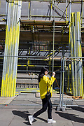 A young woman wearing yellow walks past matching coloured scaffolding on London's Southbank. In a scene of yellows, we see the construction site with stacked scaffold poles with their ends and middles making it a safe material to erect on the sides of buildings.