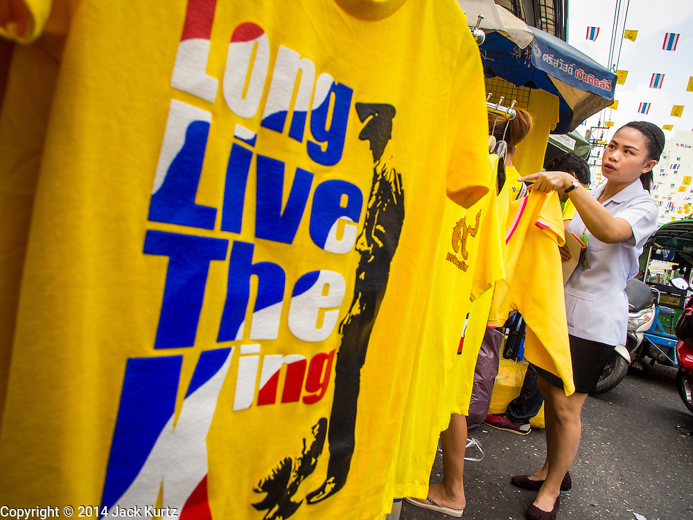 "28 NOVEMBER 2014 - BANGKOK, THAILAND: A woman in Bangkok looks at tee shirts that say ""Long Live the King"" before the King's Birthday in Thailand. Bhumibol Adulyadej, the King of Thailand, was born on December 5, 1927, in Cambridge, Massachusetts. The family was in the United States because his father, Prince Mahidol, was studying Public Health at Harvard University. He has reigned since 1946 and is the world's currently reigning longest serving monarch and the longest serving monarch in Thai history. Bhumibol, who is in poor health, is revered by the Thai people. His birthday is a national holiday and is also celebrated as Father's Day. He is currently hospitalized in Siriraj Hospital, recovering from a series of health setbacks. Thousands of people come to the hospital every day to sign get well cards for the King. People wear yellow at events associated with the King because he was born on a Monday, and yellow is Monday's color in Thai culture. It's also the color of the monarchy.       PHOTO BY JACK KURTZ"