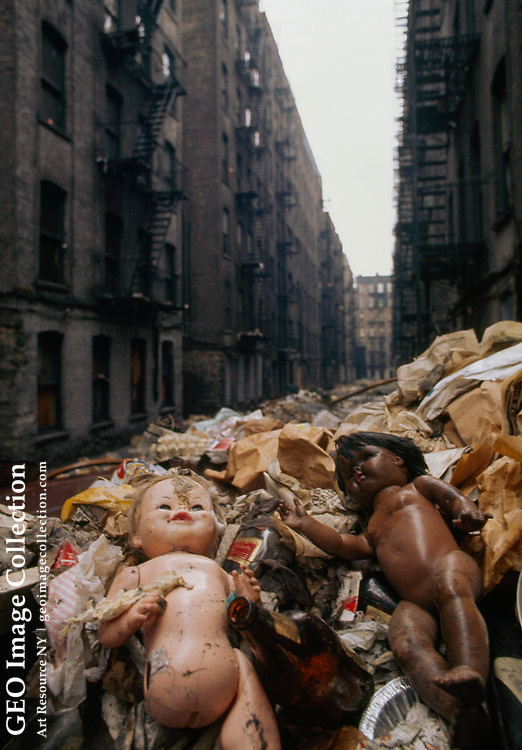 Trash fills an alley behind crowded tenements.