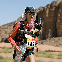 27 March 2007:  #163 Geraldine Courdesses, 2006 winner of the women race, runs across the gorge of El Maharch during third stage of the 22nd Marathon des Sables between jebel El Oftal and jebel Zireg (20.07 miles). The Marathon des Sables is a 6 days and 151 miles endurance race with food self sufficiency across the Sahara Desert in Morocco. Each participant must carry his, or her, own backpack containing food, sleeping gear and other material.