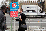 A campaigner wears a Margaret Thatcher face-mask in Parliament Square during the week-long protest by climate change activists with Extinction Rebellion's campaign to block road junctions and bridges around the capital, on 23rd April 2019, in London England.