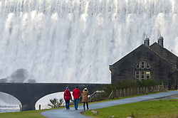 © Licensed to London News Pictures. 11/02/2019. Elan Valley, Powys, Wales, UK. Visitors arrive to see the dam. Water cascades over the Caban-coch dam, at Elan Valley village near Rhayader in Powys, Wales, UK after recent torrential rain in Powys has filled the complex of Elan valley dams and taken river levels to the tops of river banks in Powys, Wales, UK. Elan Valley dams supply Birmingham in the West Midlands UK with water via a gravity feed. credit: Graham M. Lawrence/LNP