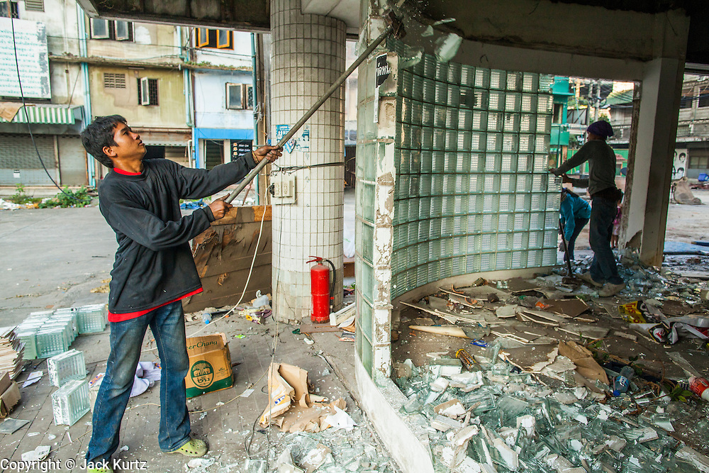 """13 DECEMBER 2012 - BANGKOK, THAILAND:   Workers knock out glass blocks in a corner office at """"Washington Square"""" a notorious entertainment district off Sukhumvit Soi 22 in Bangkok. Demolition workers on many projects in Thailand live on their job site tearing down the building and recycling what can recycled as they do so until the site is no longer inhabitable. They sleep on the floors in the buildings or sometimes in tents, cooking on gas or charcoal stoves working from morning till dark. Sometimes families live and work together, other times just men. Washington Square was one of Bangkok's oldest red light districts. It was closed early 2012 and is being torn down to make way for redevelopment.    PHOTO BY JACK KURTZ"""