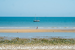 Bridlington North Beach A couple walk down the beach past a  Yacht sitting out in the bay<br /> <br />   05 July 2018 <br />   Copyright Paul David Drabble<br />   www.pauldaviddrabble.co.uk