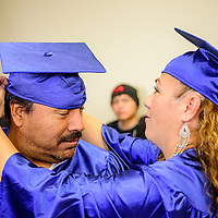 060515  Adron Gardner/Independent<br /> <br /> Rosendo Soto, left, receives help with his graduation cap from Griselda Ortiz before the New Life Learning GED program gradutaion at the Lighthouse Church in Gallup Friday.