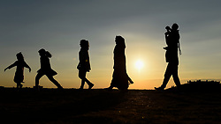 © Licensed to London News Pictures. 01/09/2018. LONDON, UK.  A family walk on one of the manmade mounds at Northala Fields near Northolt in west London as the sun sets on the first day of the meteorological autumn.  The forecast is for a few more warm days before temperatures start to cool.  Photo credit: Stephen Chung/LNP