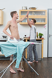 Man ironing clothes while another man cooking in background