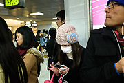 Commuter on her smart phone wearing a surgical mask in Shinjuku station. Shinjuku is used by 3.64 million passengers a day making it the busiest transport hub in the world. Tokyo, Japan.