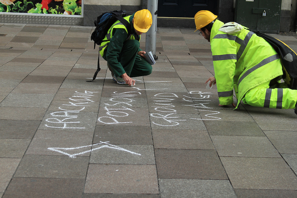 Frack Free Wales protest, Cardiff. Protesters use to chalk to write 'fracking pollutes ground water'