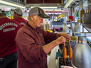 30 JULY 2019 - DES MOINES, IOWA:   EVA KUHL, a worker with Westmoreland Concessions, makes corn dogs in their booth on the Iowa State Fair fairgrounds. The Iowa State Fair Is one of the largest state fairs in the United States and runs for 10 days. In 2019, it runs from August 8 to 18. More than one million people attend the fair every year. Most of the food concessions at the fair don't open until August 3, when exhibitors arrive, but the Westmoreland Concessions corn dog stand opened on July 28. Kuhl said a lot of people drive out to the fairgrounds the week before the fair to buy corn dogs because the fair is so crowded and concession lines are very long.     PHOTO BY JACK KURTZ