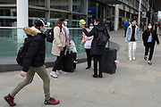 As the UK government urged that all Britons should avoid non-essential travel abroad in order to combat the Coronavirus pandemic in Britain, recently arrived passengers wearing face masks check their journeys outside St. Pancras rail station, the terminus for Eurostar services to mainland Europe, on 17th March 2020, in London, England.