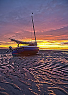 A catboat  resting on the tidal flats at Saint's Landing in Brewster points to the setting sun.