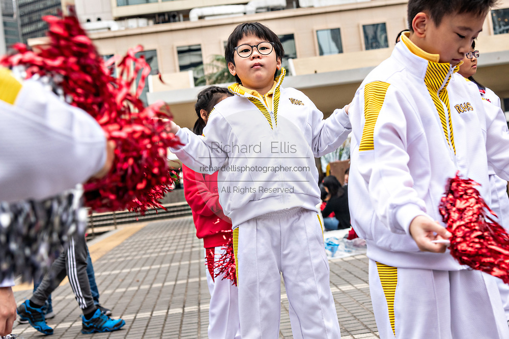 Young Chinese children rehearse cheerleading routines at Statue Square in Central District, Hong Kong.