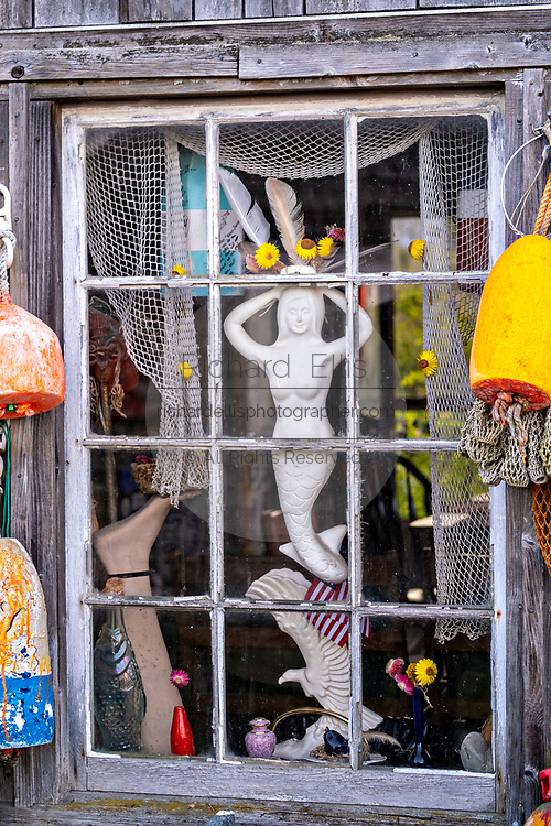 A mermaid decorates the window on an old boat house in the quaint fishing harbor of Port Clyde, Maine.