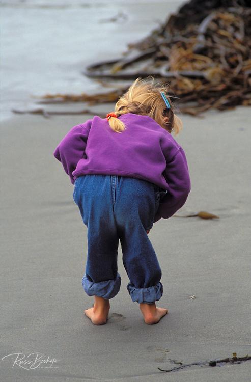 Child (age 3) beachcombing on Sand Dollar Beach, Big Sur Coast, Los Padres National Forest, California