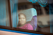 16 JUNE 2014 - POIPET, CAMBODIA: Cambodian migrants look out the windows of the bus that brought them back to Cambodia from Thailand. More than 150,000 Cambodian migrant workers and their families have left Thailand since June 12. The exodus started when rumors circulated in the Cambodian migrant community that the Thai junta was going to crack down on undocumented workers. About 40,000 Cambodians were expected to return to Cambodia today. The mass exodus has stressed resources on both sides of the Thai/Cambodian border. The Cambodian town of Poipet has been over run with returning migrants. On the Thai side, in Aranyaprathet, the bus and train station has been flooded with Cambodians taking all of their possessions back to Cambodia.   PHOTO BY JACK KURTZ