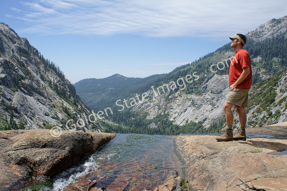 A hiker takes in the view from the top of the waterfalls below Sequoia's Hamilton Lake.<br /> <br /> This is the only trail in the High Sierras with a tunnel.