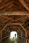 Trusses and beams in geometric shapes and man walking dogs at The Old Covered Bridge, bridge by Sheffield Plain, Massachusetts.
