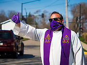 "05 APRIL 2020 - DES MOINES, IOWA:  Rev. RUSSELL LACKEY blesses people in the neighborhood around Grand View University after a drive through Palm Sunday service sponsored by Luther Memorial Church on the campus of Grand View University in Des Moines. About 150 people attended the service. They remained in their cars while the ministers read a short passage from the Bible, handed out palms and blessed them. On Sunday, 05 April, Iowa reported 868 confirmed cases of the Novel Coronavirus (SARS-CoV-2) and COVID-19. There have been 22 deaths attributed to COVID-19 in Iowa. Restaurants, bars, movie theaters, places that draw crowds are closed until 30 April. The Governor has not ordered ""shelter in place"" but several Mayors, including the Mayor of Des Moines, have asked residents to stay in their homes for all but essential needs. People are being encouraged to practice ""social distancing"" and many businesses are requiring or encouraging employees to telecommute.       PHOTO BY JACK KURTZ"