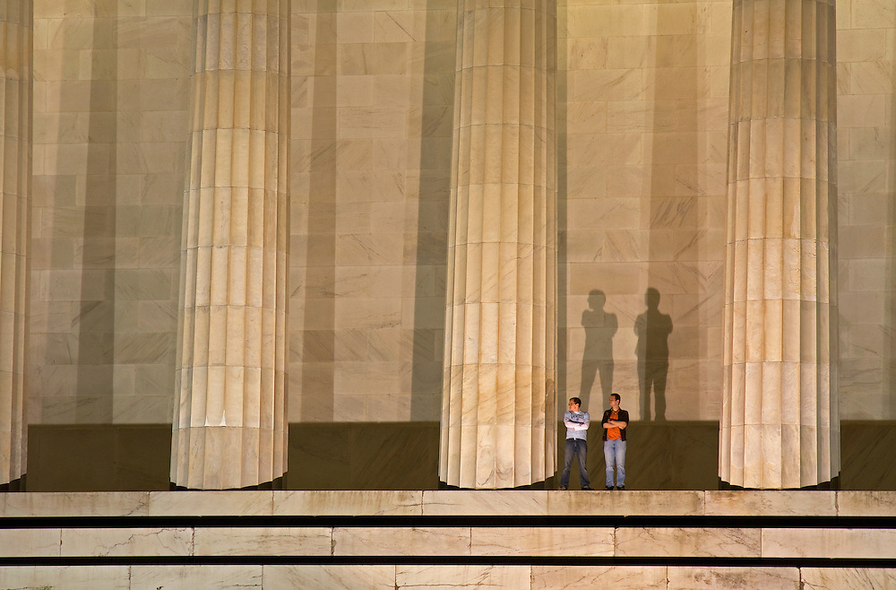Seemingly unaware, these tourists cast monumental shadows at the Lincoln Memorial, honoring the 16th President of the United States. Located on the National Mall in Washington, DC, the monument contains a large seated sculpture of Abraham Lincoln and inscriptions of two well-known speeches by Lincoln, The Gettysburg Address and his Second Inaugural Address.