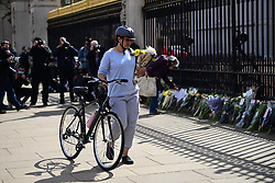 © Licensed to London News Pictures. 09/04/2021. London, UK. Members of the public place flowers outside Buckingham Palace. The British Royal Family have announced the death of Prince Philip, The Duke of Edinburgh, at the age of 99. Photo credit: Ben Cawthra/LNP