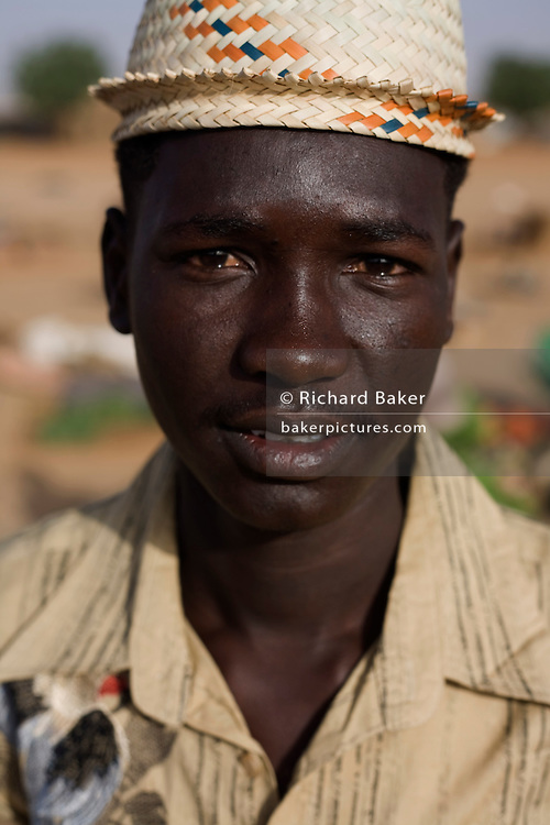 Close-up face of a fruit seller in the 4 sq km Abu Shouk refugee camp which is (disputedly) home to 38,000 displaced persons and families on the outskirts of the front-line town of Al Fasher (also spelled, Al-Fashir) in north Darfur.