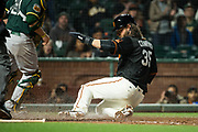 San Francisco Giants shortstop Brandon Crawford (35) slides into home plate to score against the Oakland Athletics at AT&T Park in San Francisco, California, on March 30, 2017. (Stan Olszewski/Special to S.F. Examiner)