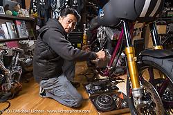 Yutaka Nishida wrenching on a custom in his Joyride Speed Shop. Kodaira City, Tokyo, Japan. Friday December 8, 2017. Photography ©2017 Michael Lichter.
