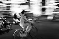 Woman riding a bicycle amongst the craziness of Saigon traffic at night.
